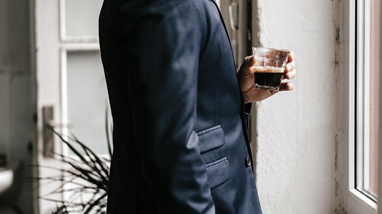 Eine Person im Anzug hält ein kleines Glas Kaffee in der Hand.