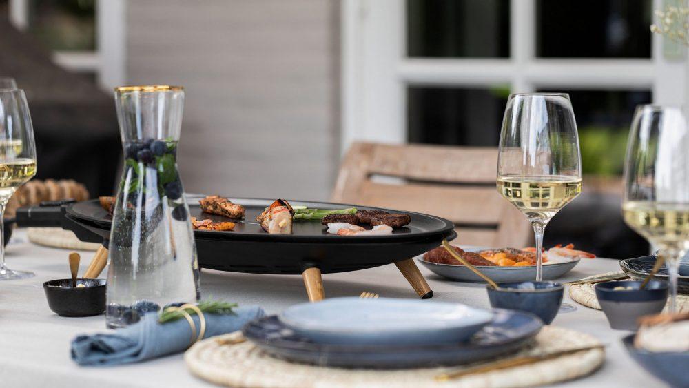 Ein Teppanyakigrill steht auf einem gedeckten Tisch vor einem Haus.