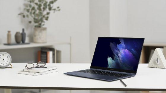 Ein aktuelles Galaxy Book Pro steht auf einem Tisch, daneben sind Notizblöcke und eine Brille zu sehen.