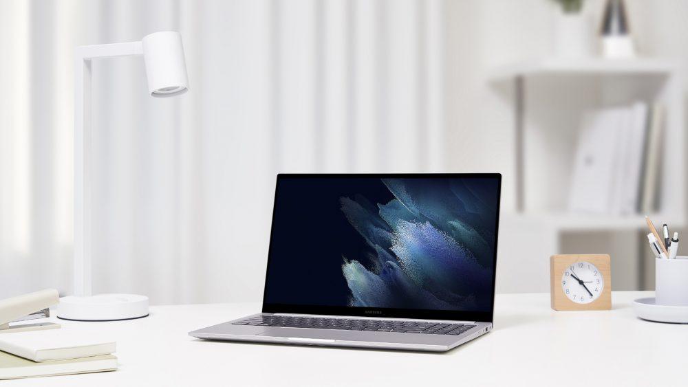 Ein Galaxy Book steht aufgeklappt auf einem Tisch neben einer Schreibtischlampe.