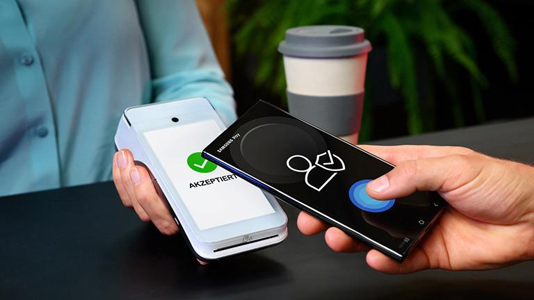Ein Smartphone wird an ein Kartenlesegerät für einen kontaktlosen Bezahlvorgang gehalten.
