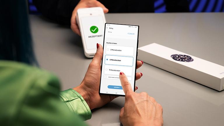 Eine Frau hält ein Smartphone in der Hand. Auf dem Display ist Samsung Pay zu erkennen. Im Hintergrund hält eine weitere Hand ein Kartenlesegerät in ihre Richtung.