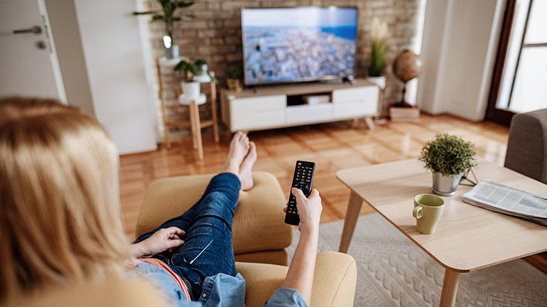 Eine Person sitzt auf einem Sessel mit einer Fernbedienung in der Hand und schaut Fernsehen.