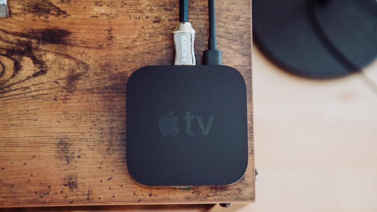 Ein Apple TV steht auf einem Lowboard aus Naturholz.