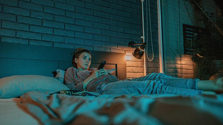 Eine Person liegt im Bett und hat eine Fernbedienung in der Hand. Sie schaut auf einen Fernseher, der nicht im Bild ist.