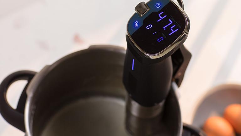 Ein Sous-vide-Stick steckt in einem Topf mit Wasser, das Display zeigt 47,4 Grad Celsius an.