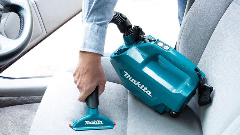 Der Makita CL121DSA im Einsatz. Eine Person saugt damit den Fahrersitz eines Autos ab.