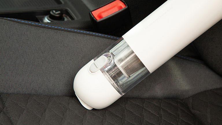 Der Xiaomi Mi Vacuum Cleaner Mini saugt entlang der Längsnaht auf der Sitzfläche eines Autositzes.