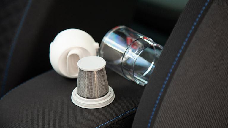 Düse, Filter und Auffangbehälter des Xiaomi Mi Vacuum Cleaner Mini liegen ausgebaut auf der Armlehne eines Autos.
