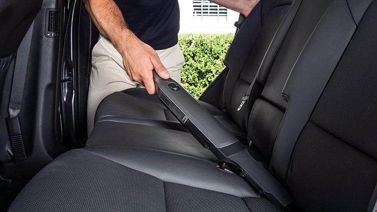 Eine Person saugt mit dem Shark WV251EU in die Ritze zwischen Lehne und Sitzteil auf der Rücksitzbank eines Autos.