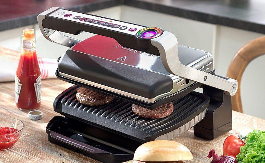 Ein Tefal Optigrill mit eingelegten Burger-Patties auf einem Küchentisch.