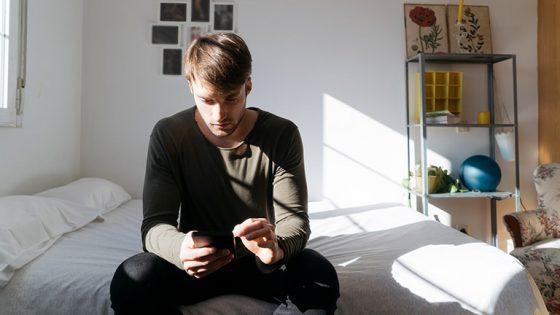 Eine Person sitzt auf einem Bett und bedient ihr Smartphone.