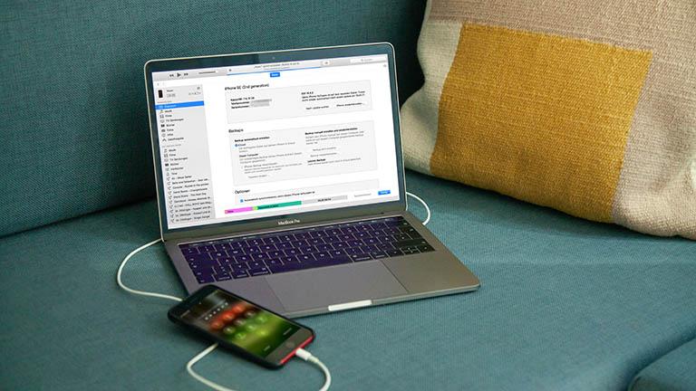 Eine iPhone ist per Kabel an ein MacBook Pro angeschlossen, auf dem iTunes geöffnet ist.