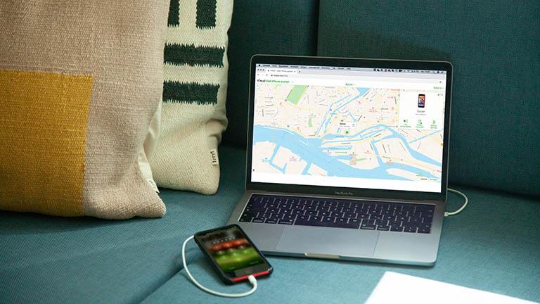 Ein iPhone ist per Kabel an ein MacBook Pro angeschlossen. Darauf ist die Gerätesuche von iCloud geöffnet.