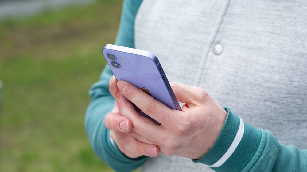 ine Person hält das iPhone 12 in der neuen Farbe Violett in den Händen.