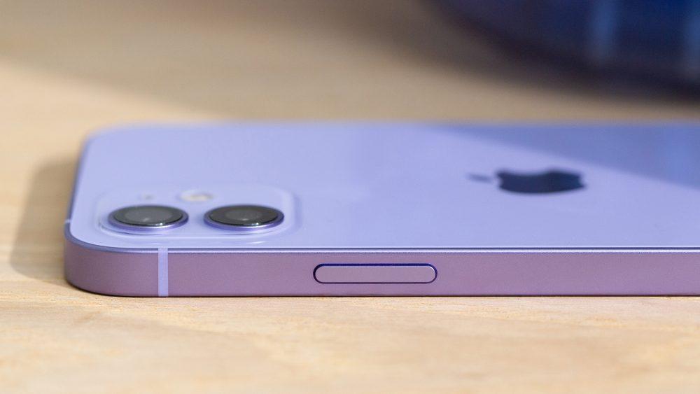 Das iPhone 12 liegt bäuchlings auf einem Holztisch. Zu erkennen ist die Einschalttaste im Rahmen des Smartphones und die Dualkamera auf der Rückseite.