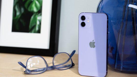 Das iPhone 12 in der neuen Farbe Violett steht auf einem Holztisch. Daneben liegt eine farblich passende Brille.