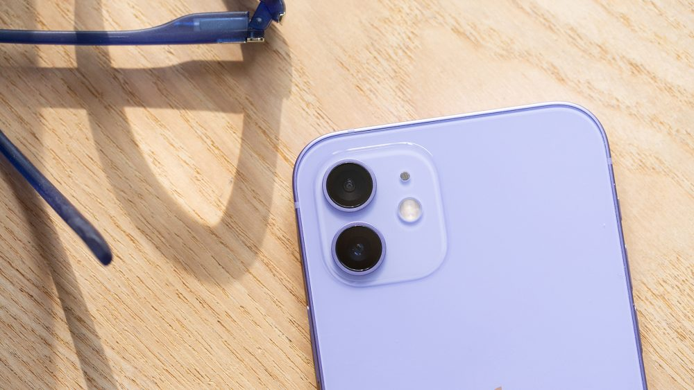 Nahaufnahme eines violetten iPhone 12. Zu sehen ist die Rückseite mit der Dualkamera und dem Blitz.