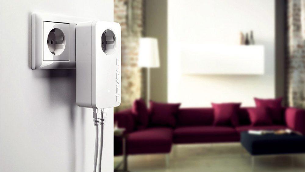 Ein devolo dLAN 550 Duo+ Powerline Adapter steckt in einer Steckdose nahe des Wohnzimmers.