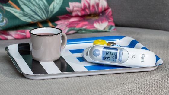 Auf einem Tablett steht eine Emailletasse mit Tee, daneben liegt ein Infrarotfieberthermometer.