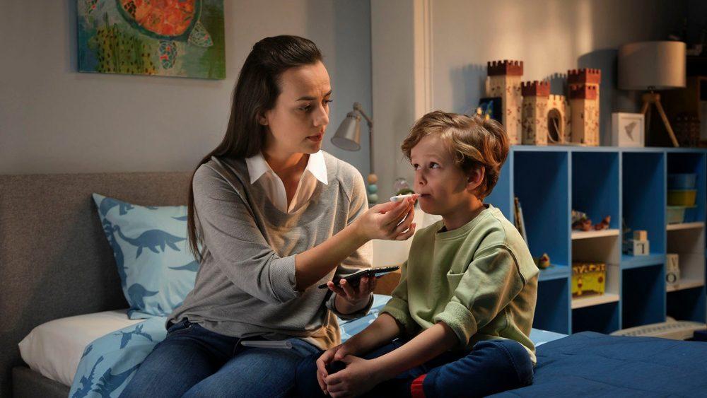 Eine Mutter sitzt mit ihrem Sohn auf der Bettkannte und hält das Fieberthermometer, das in seinem Mund steckt.