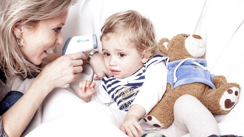 Eine Mutter misst die Temperatur bei ihrem Kind, das mit einem Kuscheltier im Bett liegt.