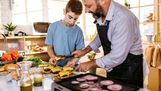 Ein Kind und eine erwachsene Person bereiten Burger vor, die sie zuvor auf einem Elektrogrill zubereitet haben.