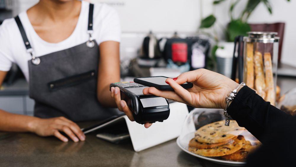 Eine Person hält ein Smartphone über ein Kartenlesegerät, um kontaktlos zu bezahlen.