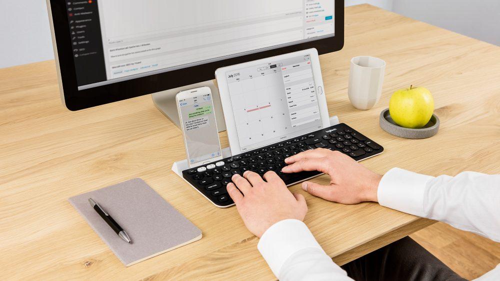 Eine Person nutzt eine Logitech K780 an einem iMac, iPhone und iPad gleichzeitig.
