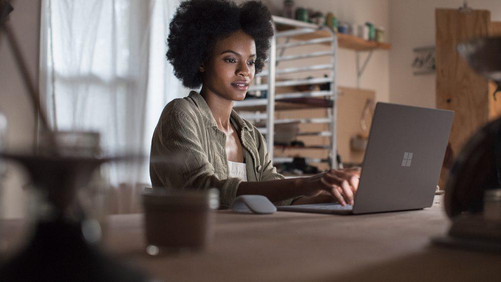 Eine Person sitzt vor einem Surface-Laptop, daneben liegt die Funkmaus Surface Arc.