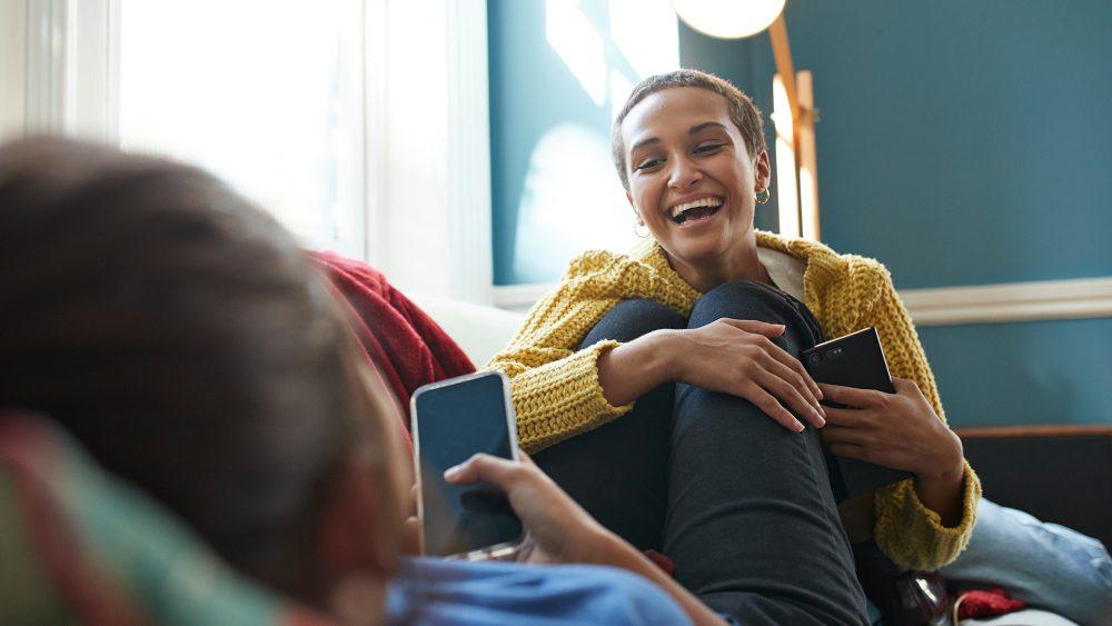 Zwei Personen auf einem Sofa, beide halten ihr Smartphone in der Hand.