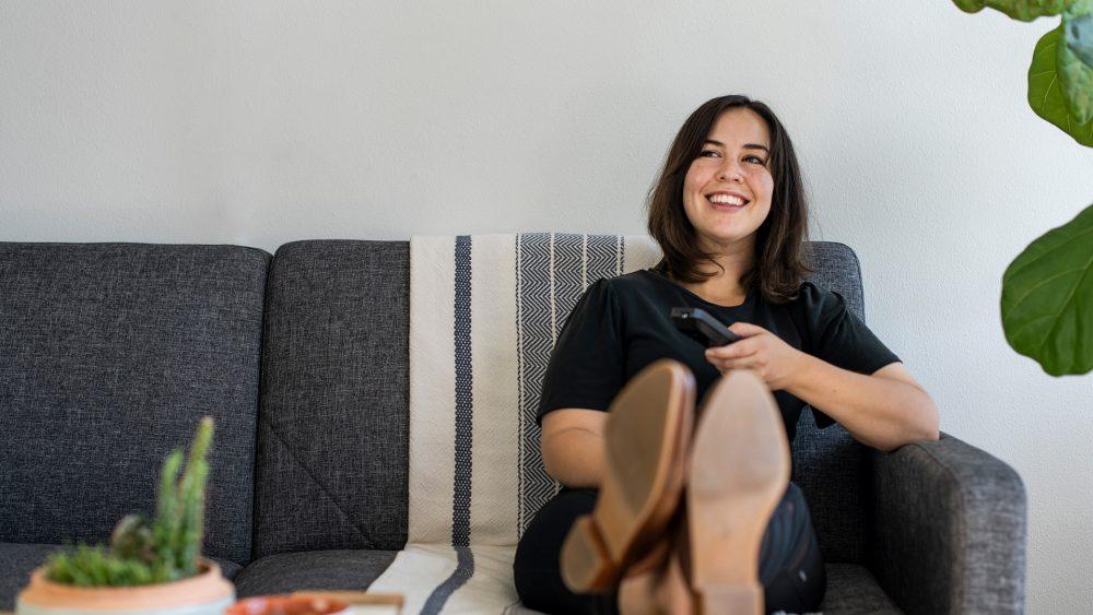 Eine Frau sitzt auf dem Sofa, legt die Beine entspannt auf dem Tisch ab und hält in der Hand eine Fernbedienung.