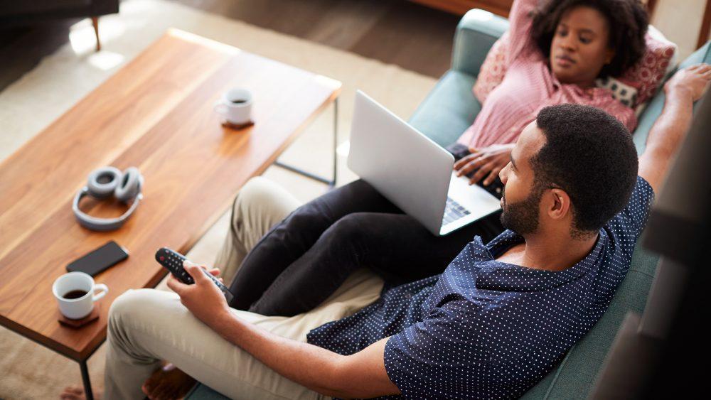 Ein Paar sitzt auf dem Sofa, ihre Beine hat sie über seine Oberschenkel gelegt, auf ihrem Schoß ein Laptop, er schaut zum Fernseher, in der Hand eine Fernbedienung.
