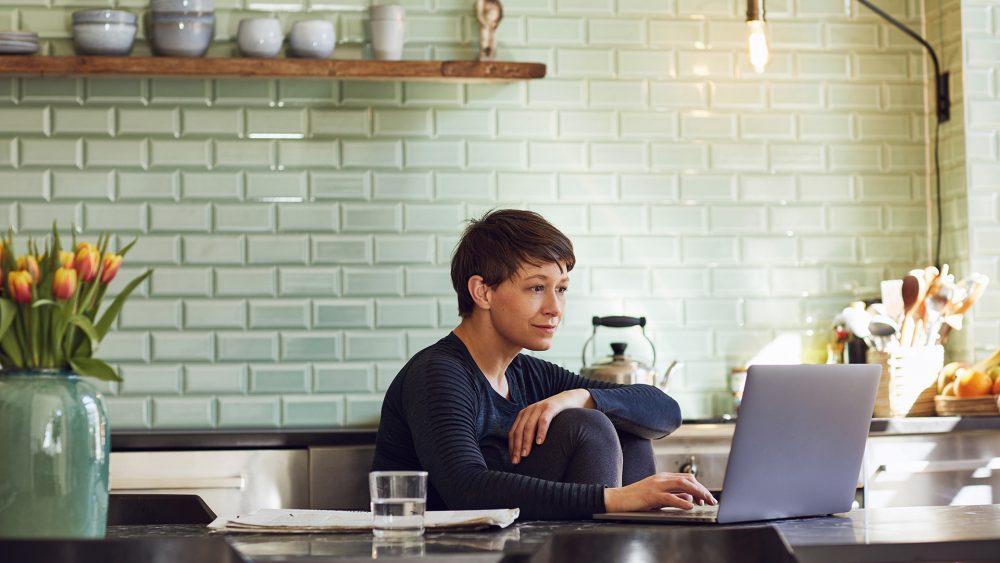 Eine Person sitzt an einem Esstisch und schaut auf einen Laptop.