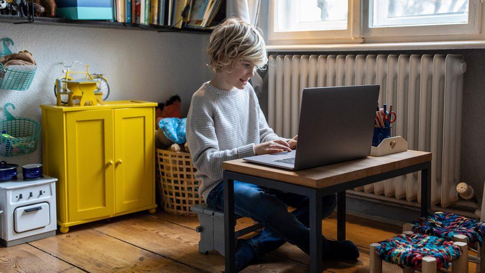 Ein Kind sitzt in seinem Zimmer vor einem Laptop.
