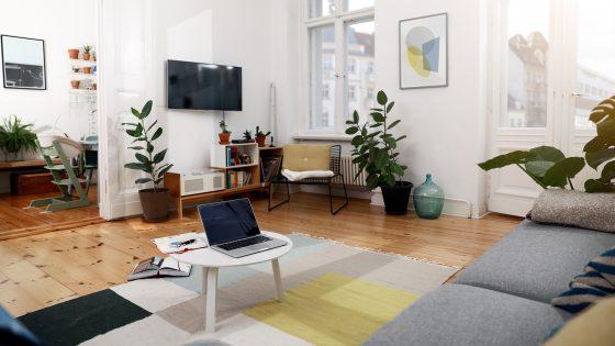Blick in ein Wohnzimmer mit einem MacBook auf dem Couchtisch und einem Fernseher an der Wand.