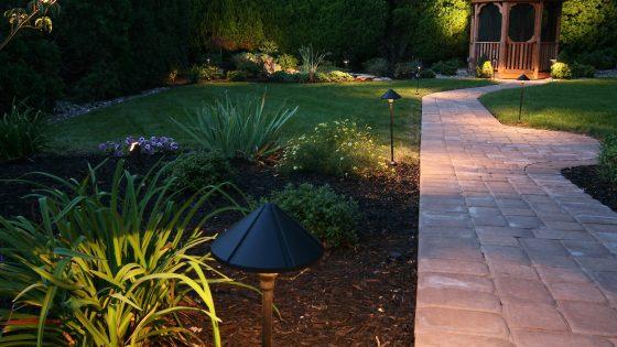 In einem illuminiertem Garten führt ein gepflasterter Weg zu einem Pavillon.