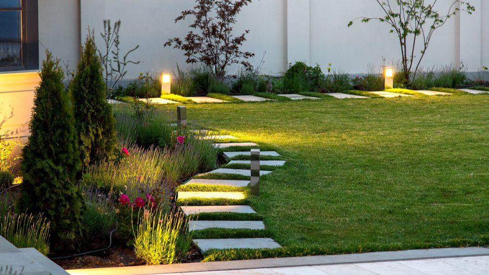 Hinter einer Rasenfläche vor einer Hauswand stehen zwei Bodenlampen.