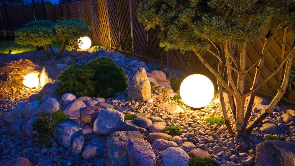 In einem Garten beleuchten mehrere runde Bodenleuchten die Beete.
