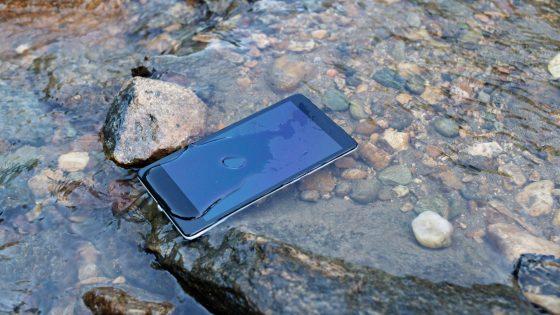 Ein Smartphone liegt in einem Bach. Es ist von Wasser bedeckt.