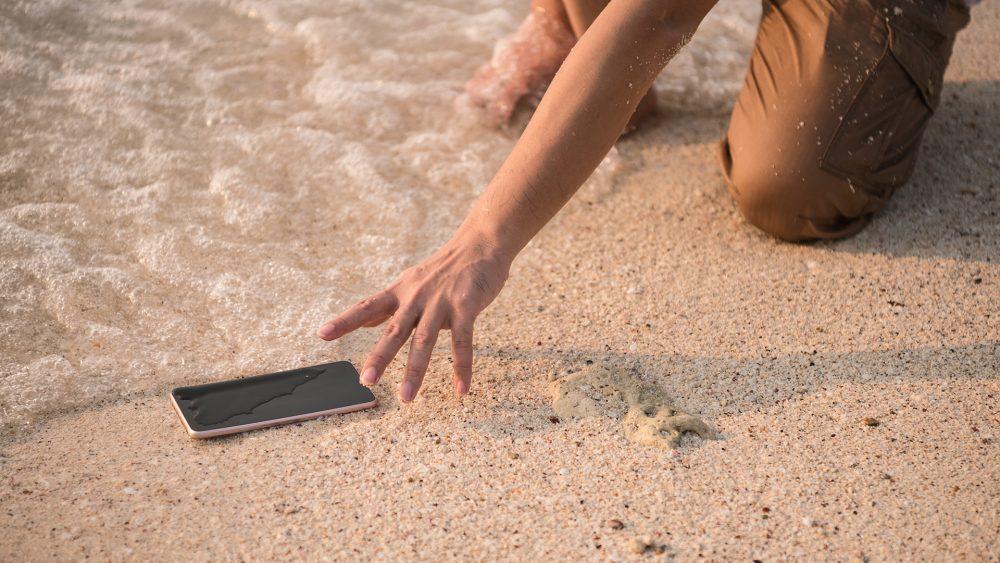 Ein Handy liegt am Strand und wird von Wasser umspült, eine Hand greift nach dem Gerät.