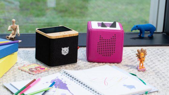 Eine schwarze Tigerbox Touch steht neben einer pinkfarbenen Toniebox, davor liegt ein Ringbuch mit Bunstiften.