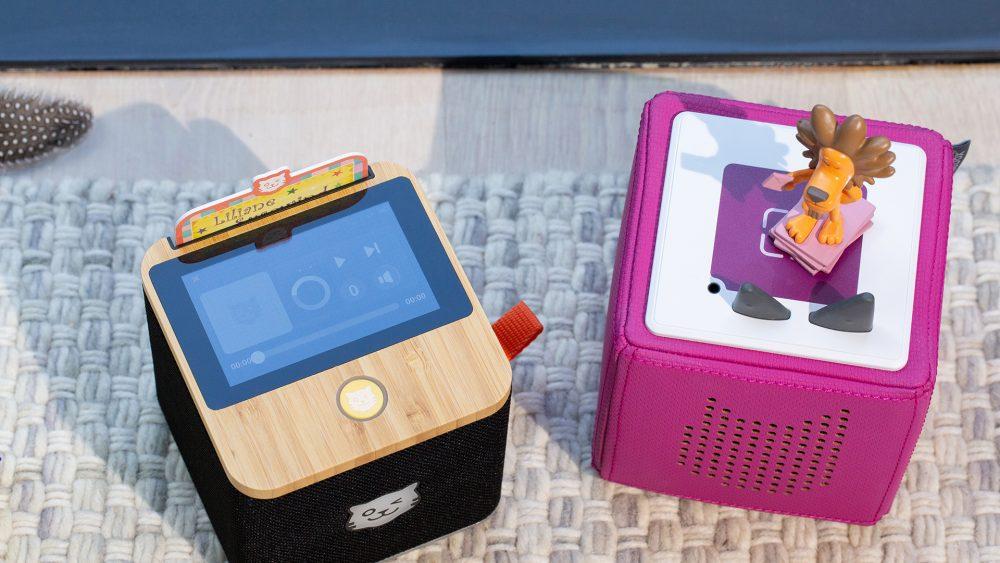 Draufsicht auf eine schwarze Tigerbox Touch und eine pinkfarbene Toniebox . Das Display der Tigerbox Touch zeigt den Player der Box.