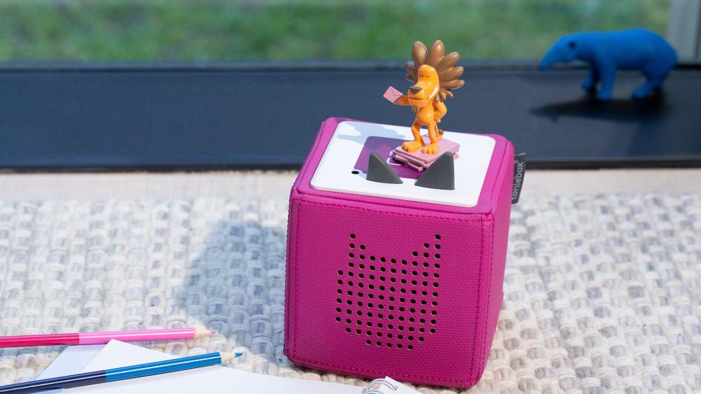 Auf einer pinkfarbenen Toniebox steht eine Toniefigur.