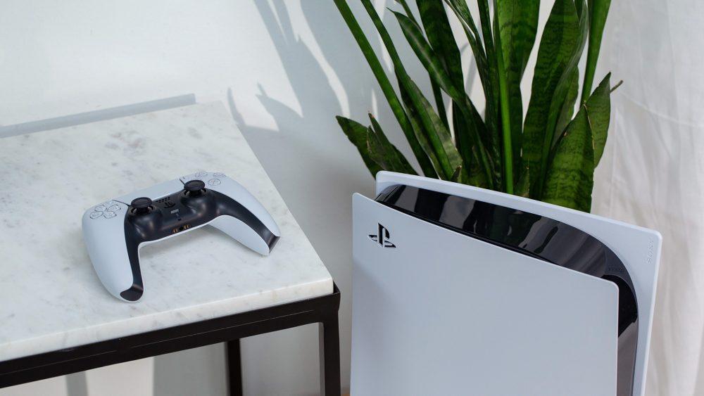 Die PlayStation 5 steht vor einer Dekopflanze. Daneben liegt der DualSense-Controller erhöht auf einem Tisch.