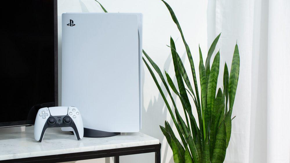 Eine PS5 steht auf einem Marmortisch neben einem Fernseher. Davor lehnt der Dualsense-Controller.