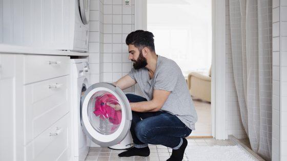In einem Badezimmer befüllt ein Mann die Waschmaschine, über der Waschmaschine steht ein Wäschetrockner