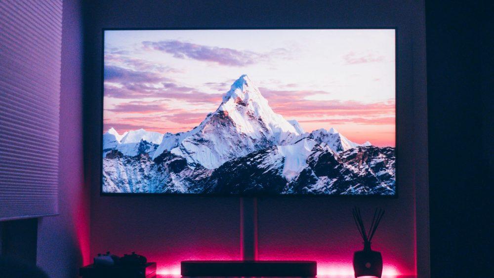 Blick auf einen großen Fernseher in einer Wohnung, auf dem ein schneebedeckter Berg zu sehen ist.