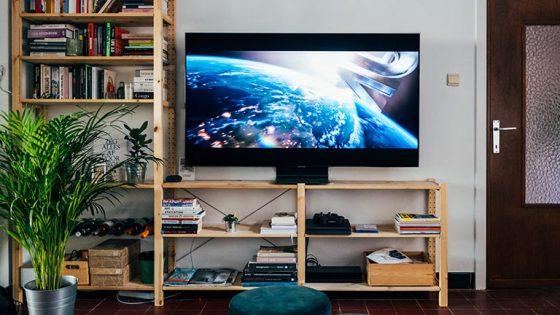 Ein Fernseher steht auf einem Holzregal. Auf dem Display läuft gerade ein Spielfilm an.