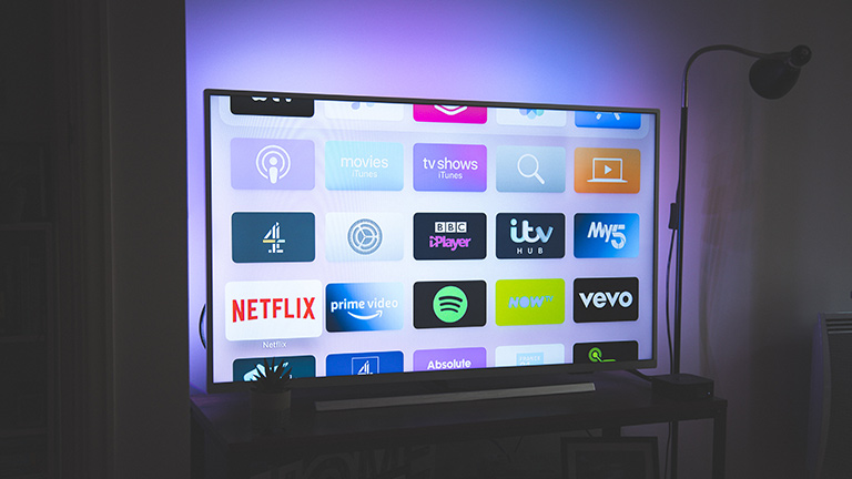 Blick auf einen Smart-TV mit Hintergrundbeleuchtung. Auf dem Display sind zahlreiche Apps zu sehen.